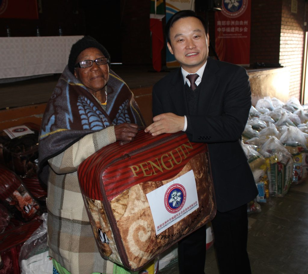 Mr Yang Peidong handing out food parcels and blankets to community members.