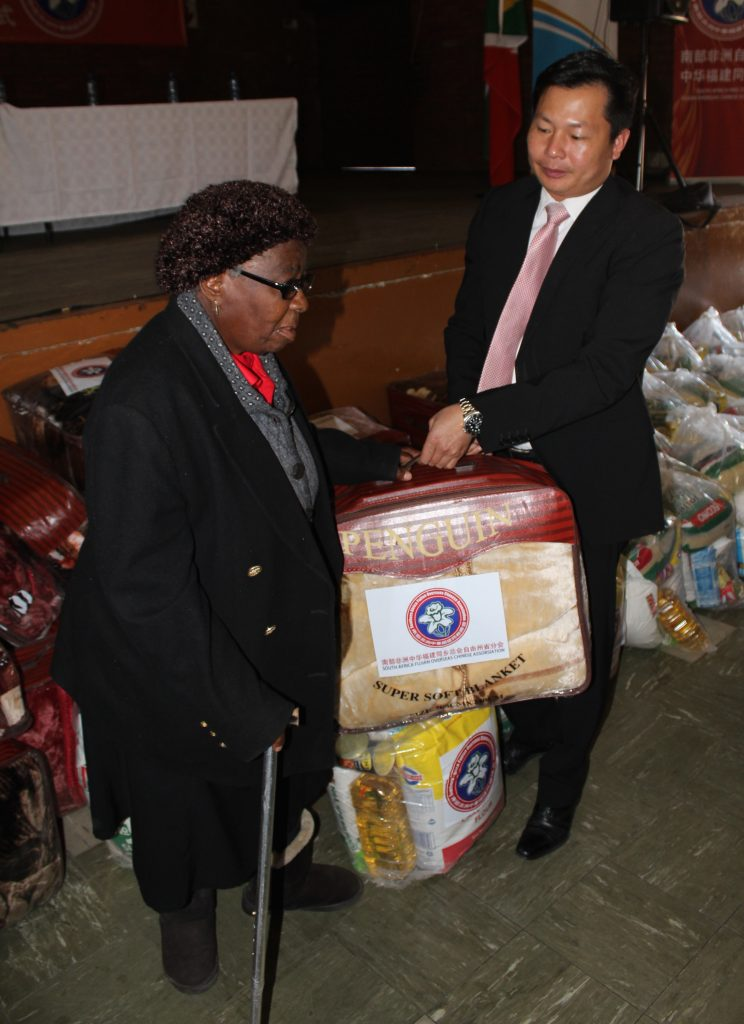 Mr Jimmy Shi handing out food parcels and blankets community members.