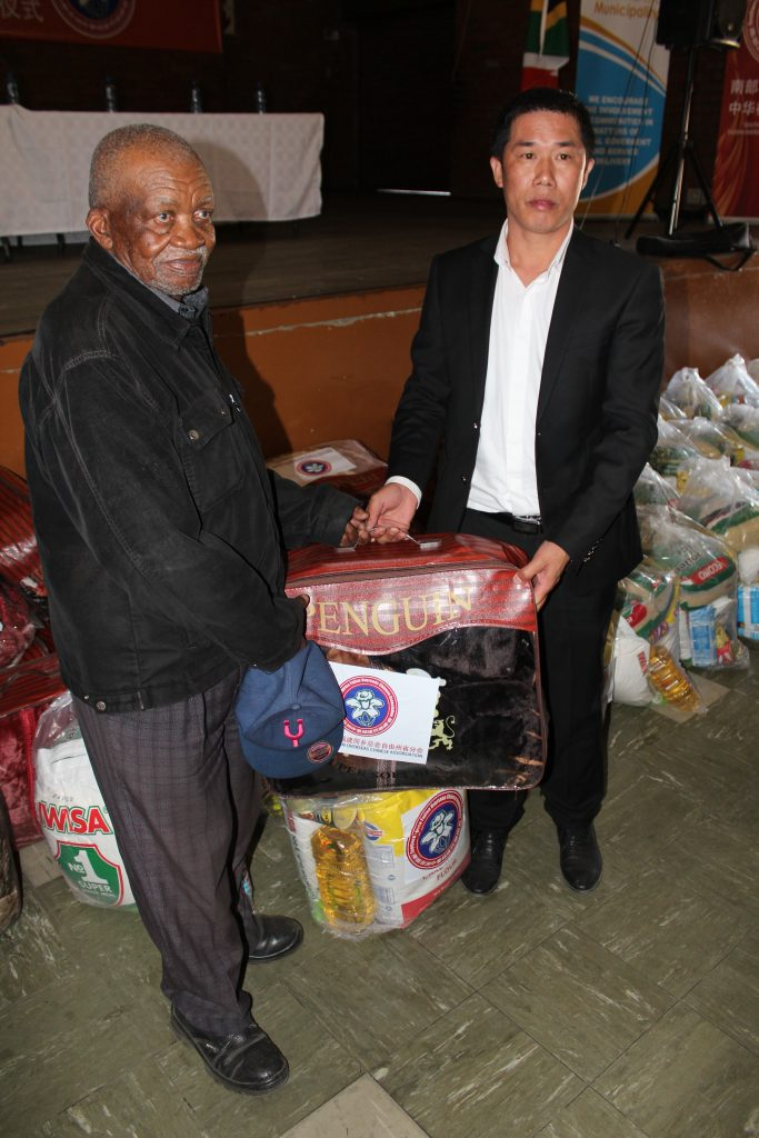 Mr Zhuang handing out food parcels and blankets community members.